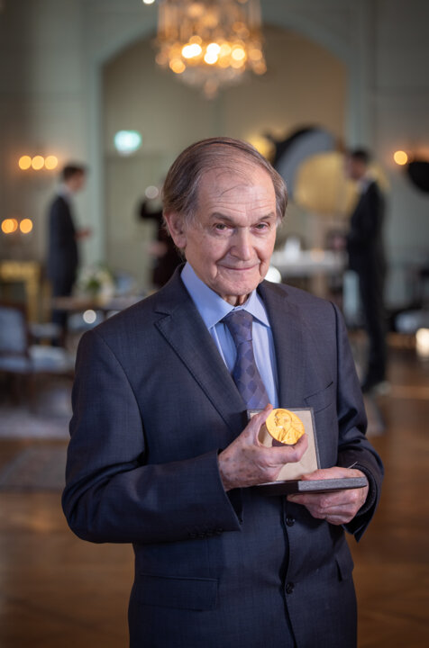 Roger Penrose showing his Nobel Prize medal at the Swedish Ambassador's Residence in London.