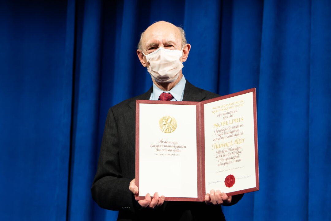 Harvey J. Alter showing his Nobel Prize diploma.