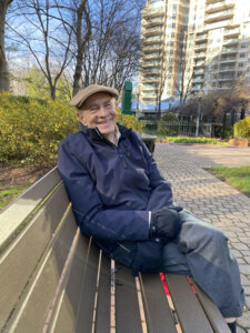 Harvey Alter sits on a bench on a sunny winter's day.