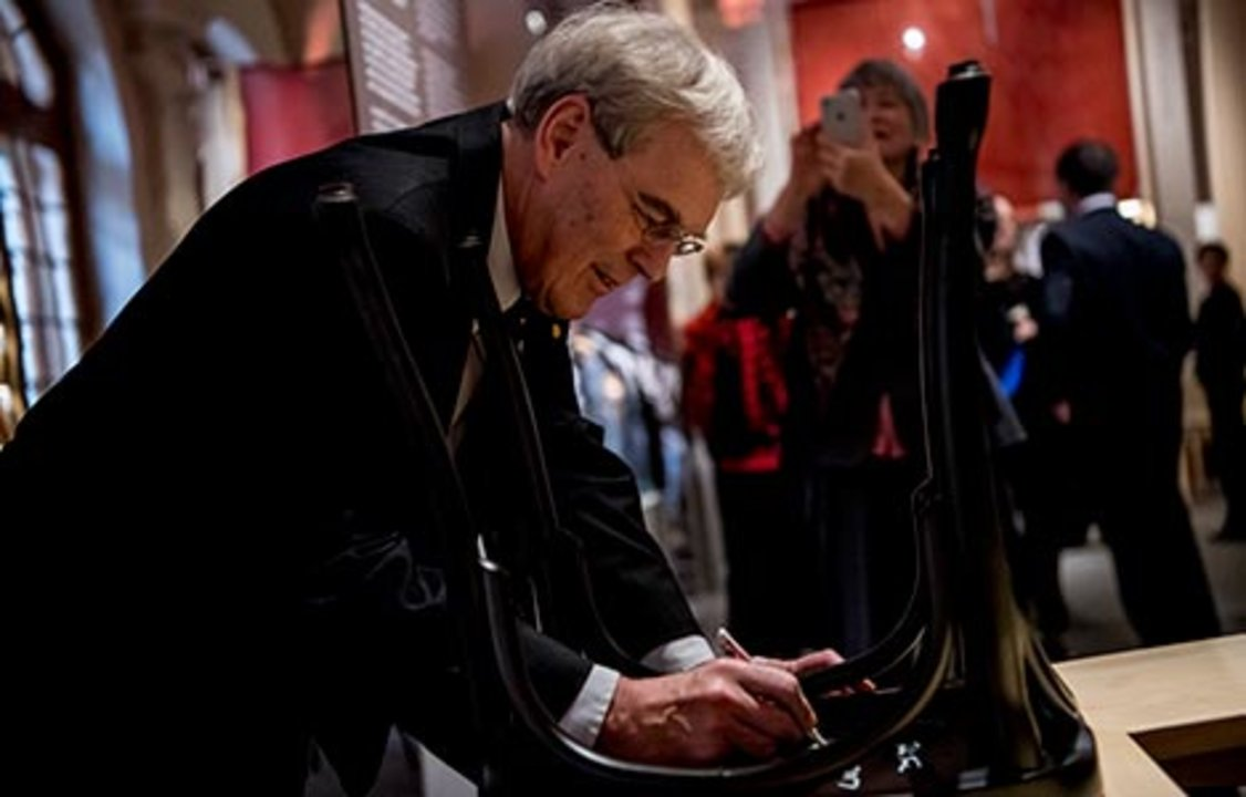 Richard Henderson autographs a chair at the Nobel Museum