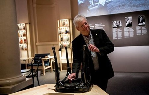 Richard H. Thaler autographs a chair at the Nobel Museum