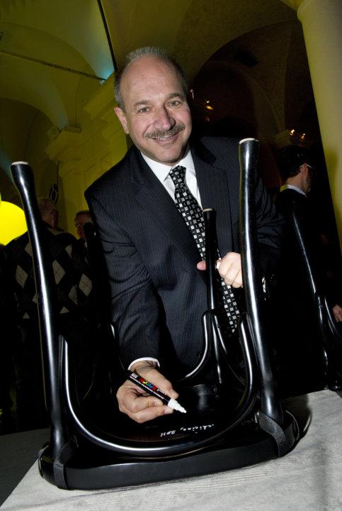 Bruce A. Beutler autographs a  chair