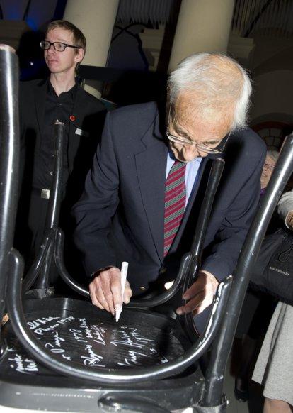 Willard S. Boyle autographs a chair