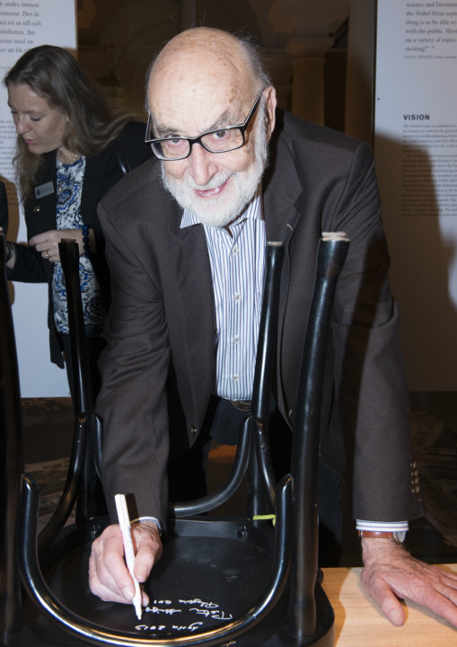 Like many Nobel Laureates before him, François Englert autographs a chair at Bistro Nobel at the Nobel Museum in Stockholm, 6 December 2013