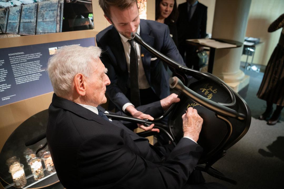 John B. Goodenough autographs a chair