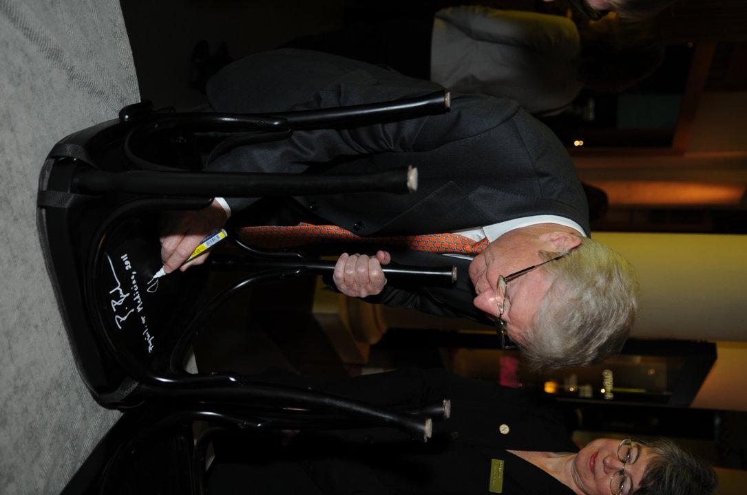 Jules A. Hoffmann autographs a chair