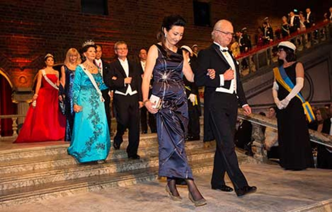 Sweden's King Carl XVI Gustaf and May-Britt Moser proceed into the Blue Hall of the Stockholm City Hall for the Nobel Banquet.