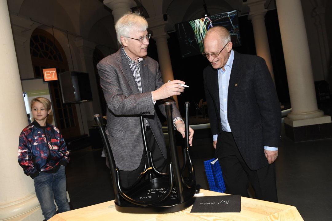Bengt Holmström and Oliver Hart autograph a chair