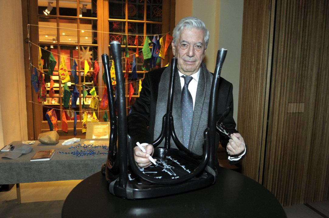 Mario Vargas Llosa autographs a chair