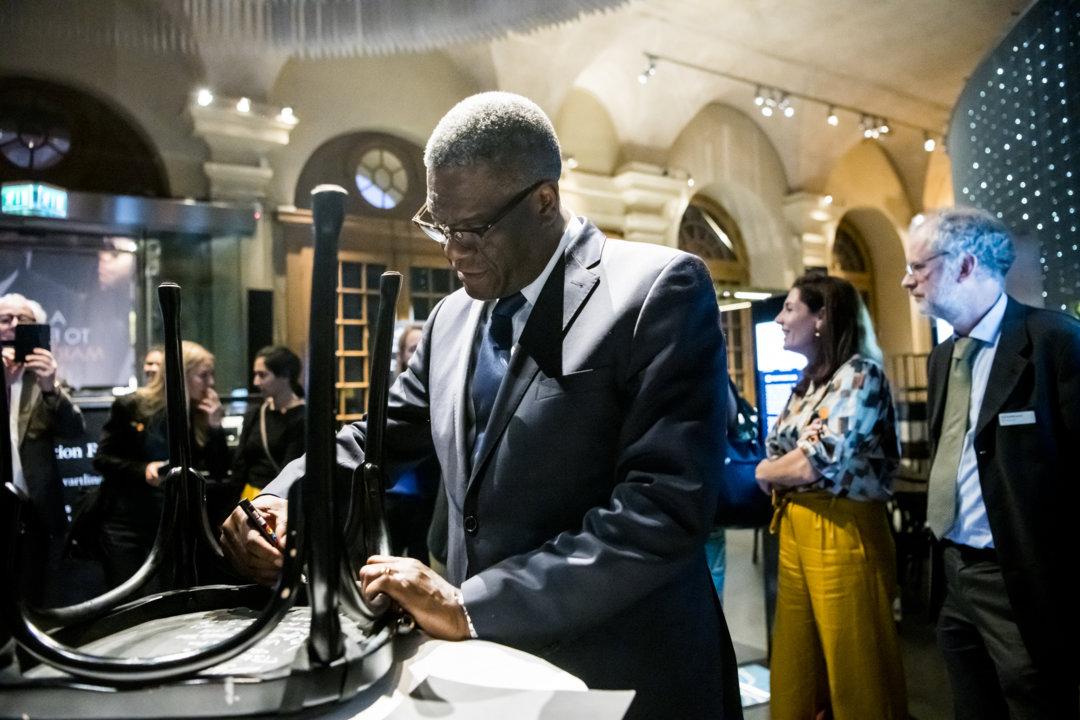 Denis Mukwege autographs a chair at the Nobel Prize Museum