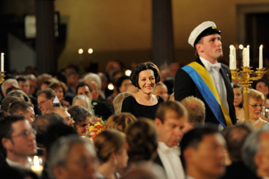 Escorted by a student, Herta Müller walks towards the podium to deliver her Banquet speech