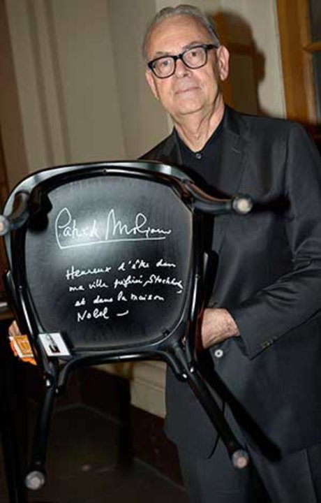 Like many Nobel Laureates before him, Patrick Modiano autographs a chair at Bistro Nobel at the Nobel Museum in Stockholm, 6 December 2014.