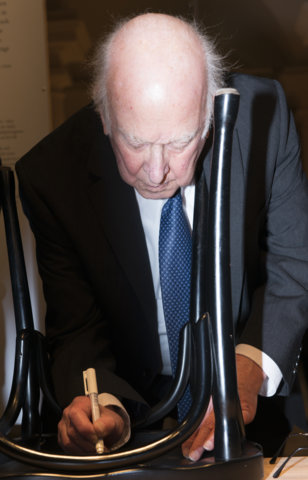 Like many Nobel Laureates before him, Peter Higgs autographs a chair at Bistro Nobel at the Nobel Museum in Stockholm, 6 December 2013