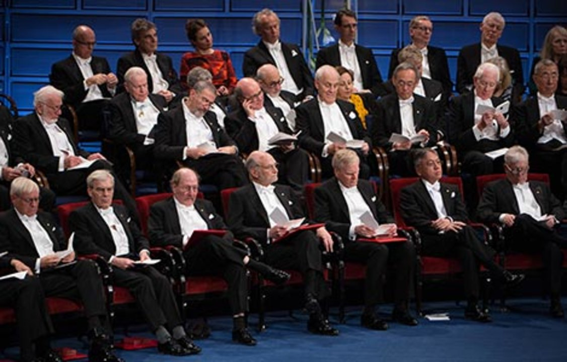 The Nobel Laureates seated on stage.