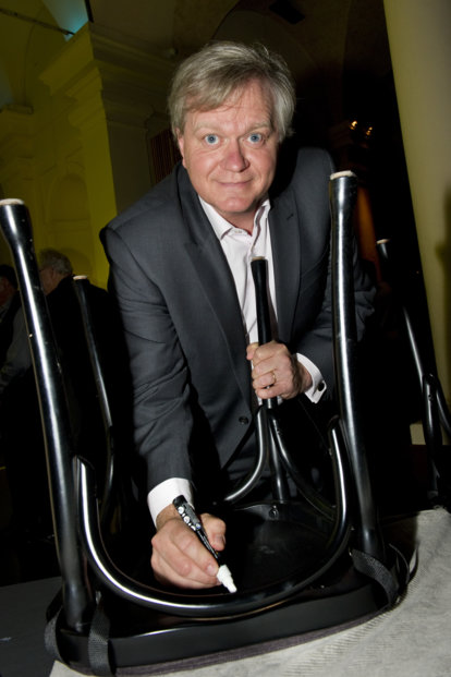Brian P. Schmidt autographs a  chair