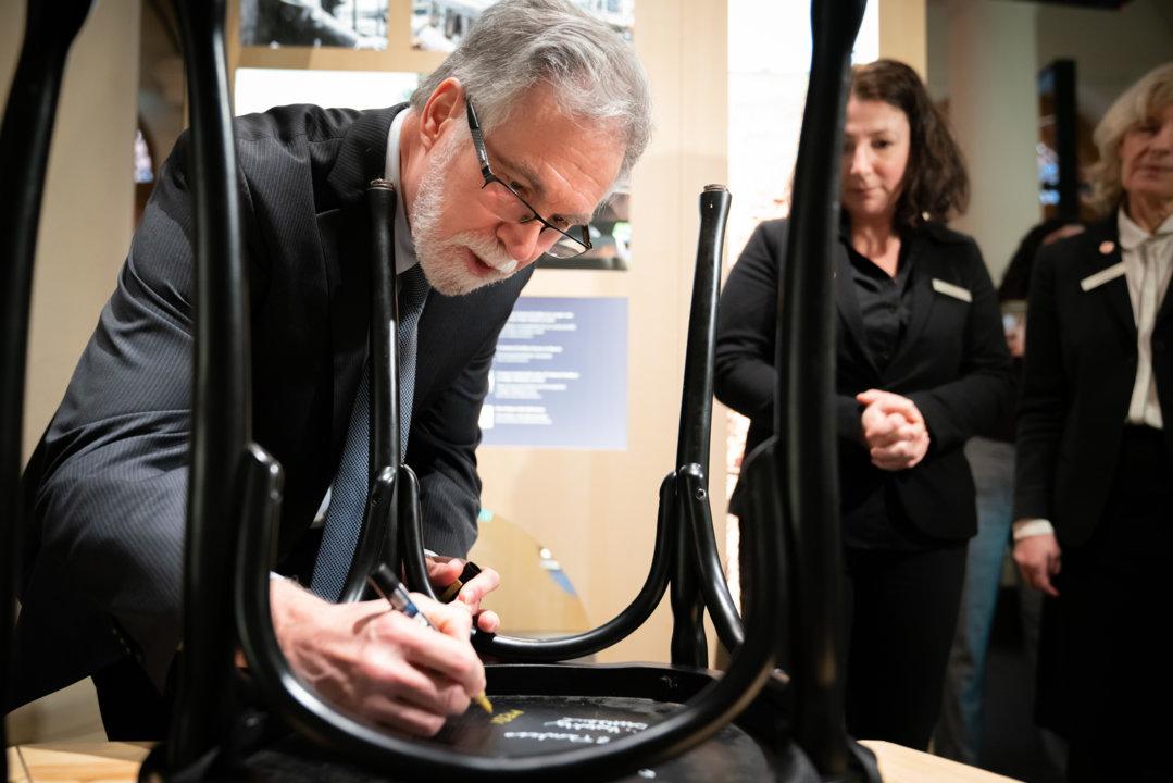 Gregg L. Semenza autographs a chair
