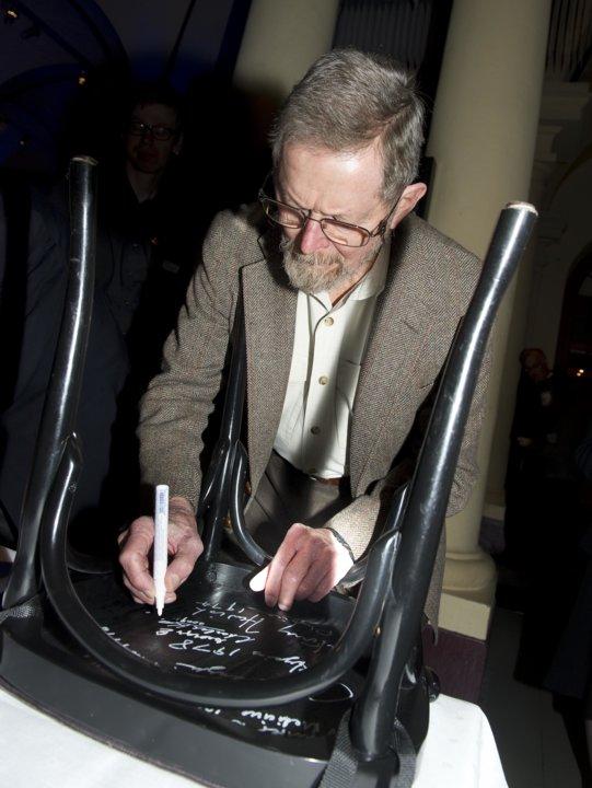 George E. Smith autographs a chair
