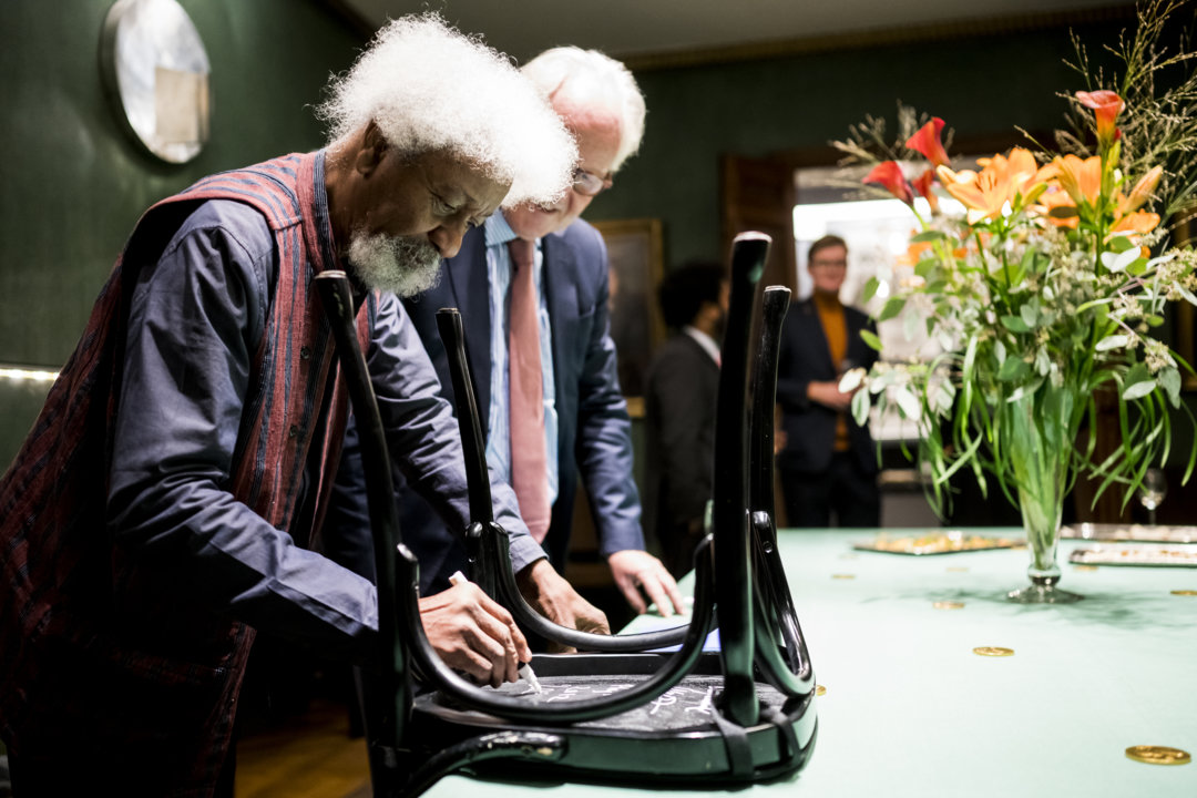Wole Soyinka autographs a chair for the Nobel Prize Museum