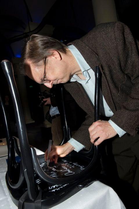 Jack W. Szostak autographs a chair