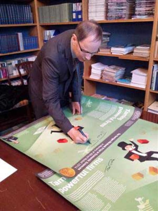 At the Royal Swedish Academy of Sciences, Jean Tirole autographs posters explaining his awarded work.