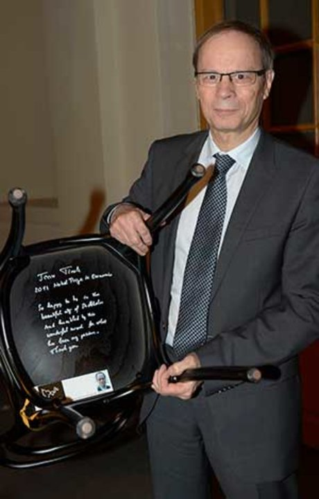 Like many Laureates before him, Jean Tirole autographs a chair at Bistro Nobel at the Nobel Museum in Stockholm, 6 December 2014.