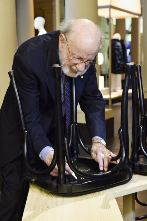 Like many Nobel Laureates before him, William C. Campbell autographs a chair at Bistro Nobel at the Nobel Museum in Stockholm.