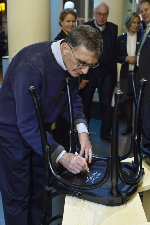 Like many Nobel Laureates before him, Aziz Sancar autographs a chair at Bistro Nobel at the Nobel Museum in Stockholm.