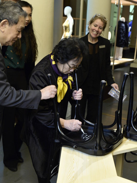 Like many Nobel Laureates before her, Youyou Tu autographs a chair at Bistro Nobel at the Nobel Museum in Stockholm.