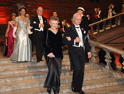 The Royal Family and other guests of honour make their entry down the stairs into the Blue Hall. His Majesty King Carl XVI Gustaf of Sweden is escorting Françoise Barré-Sinoussi.