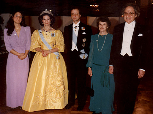 HM Queen Silvia of Sweden, radiant in a yellow gown beside HM King Carl XVI Gustaf, poses with Herbert A. Hauptman and his family