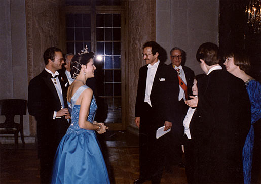 Their Majesties King Carl XVI Gustaf (left) and Queen Silvia of Sweden (her back to the camera) meet Harold Varmus and his family in the Golden Hall of the Stockholm City Hall, after the Nobel Banquet on 10 December 1989.