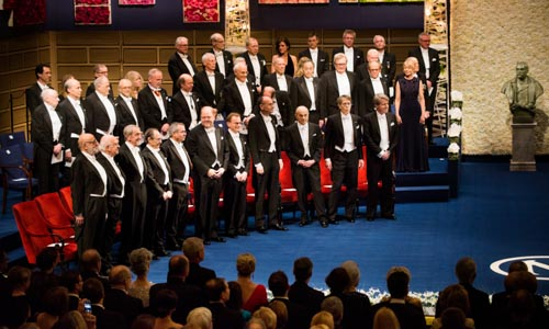 The 2013 Nobel Laureates on stage at the Nobel Prize Award Ceremony. From left: Physics Laureates François Englert and Peter Higgs, Chemistry Laureates Martin Karplus, Michael Levitt and Arieh Warshel, Medicne Laureates James E. Rothman, Randy W. Schekman and Thomas C. Südhof and Laureates in Economic Sciences Eugene F. Fama, Lars Peter Hansen and Robert J. Shiller.