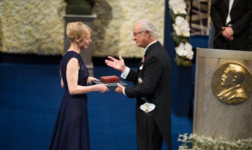 Mrs Jenny Munro receiving the Nobel Medal and Diploma on behalf of her mother Alice Munro from His Majesty King Carl XVI Gustaf of Sweden at the Stockholm Concert Hall