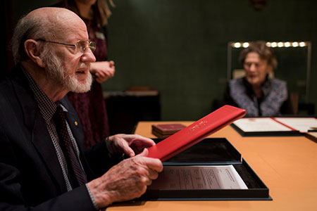 William C. Campbell takes a closer look at his Nobel diploma during his visit to the Nobel Foundation.