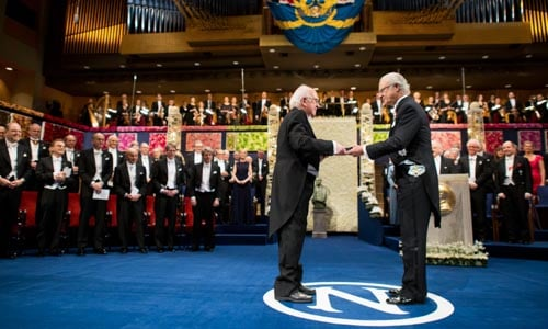 Peter Higgs receiving his Nobel Prize from His Majesty King Carl XVI Gustaf of Sweden