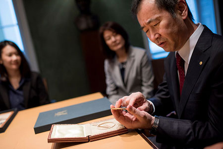 Takaaki Kajita takes a closer look at his Nobel Medal and Diploma during his visit to the Nobel Foundation on 12 December 2015.