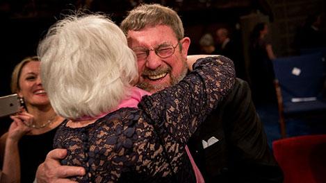 Mrs Berit Kosterlitz gives her husband a hug after the Nobel Prize Award Ceremony.