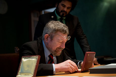 J. Michael Kosterlitz takes a closer look at his Nobel Medal during his visit to the Nobel Foundation on 12 December 2016.