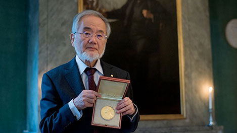 Yoshinori Ohsumi showing his Nobel Medal