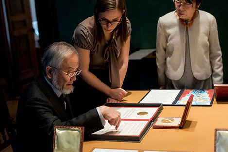 Yoshinori Ohsumi takes a look at his Nobel diploma during his visit to the Nobel Foundation