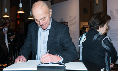 Eugene Fama writes his autograph in the guest book at the Nobel Museum in Stockholm