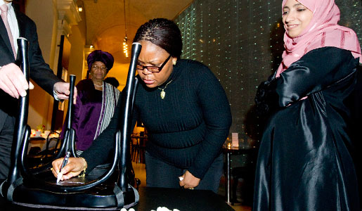 Leymah Gbowee autographs a chair at Bistro Nobel at the Nobel Museum in Stockholm