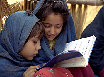 Two girls share a textbook.
