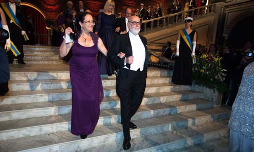 François Englert proceeds into the Blue Hall with Mrs Rina Levitt, spouse of Chemistry Laureate Michael Levitt.