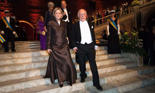 Peter Higgs and Mrs Marci Hazard, spouse of Chemistry Laureate Martin Karplus, proceed down the stairs into the Blue Hall.