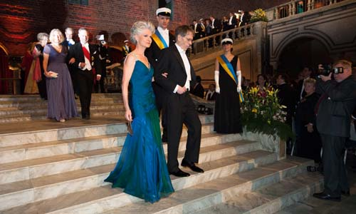 Lars Peter Hansen and Anna Maria Corazza Bildt proceed down the stairs to the Nobel Banquet in the Blue Hall of the Stockholm City Hall on 10 December 2013.