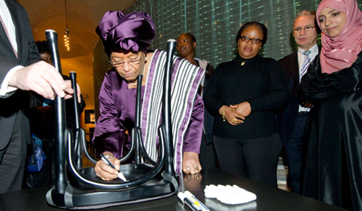 Ellen Johnson Sirleaf autographs a chair at Bistro Nobel at the Nobel Museum in Stockholm