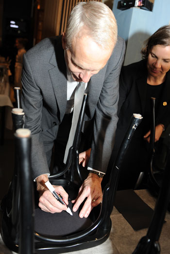 Like many Nobel Laureates before him, Brian K. Kobilka autographs a chair at Bistro Nobel at the Nobel Museum in Stockholm