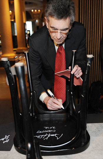 Like many Nobel Laureates before him, Robert J. Lefkowitz autographs a chair at Bistro Nobel at the Nobel Museum in Stockholm