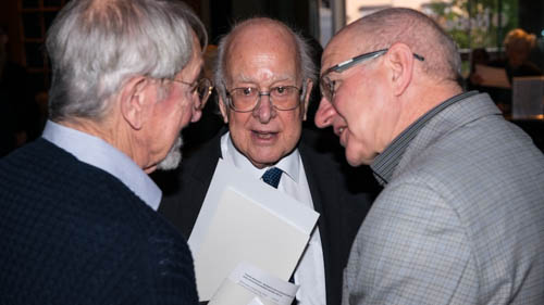 Nobel Laureates Martin Karplus (left) and Peter Higgs (middle) in a discussion at the Nobel Museum in Stockholm
